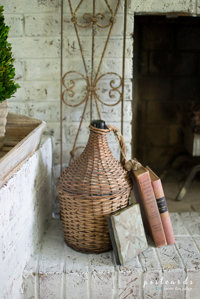old books and wicker demijohn on fireplace hearth