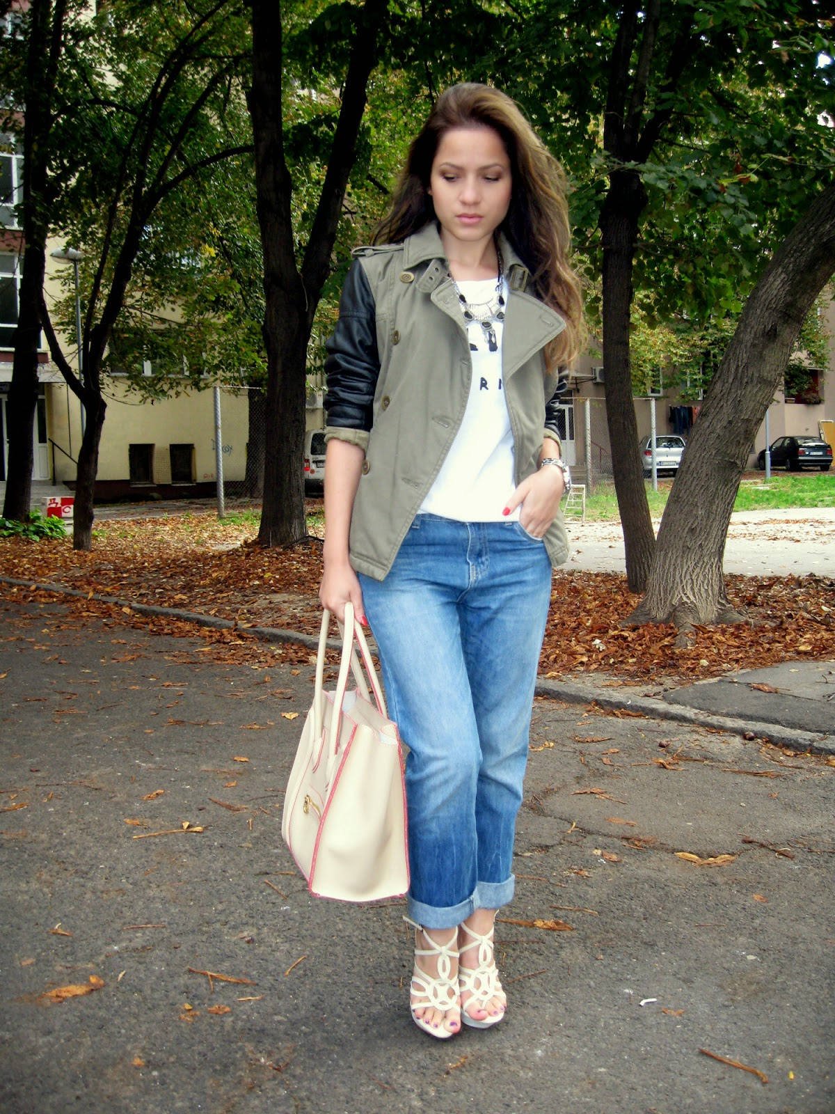 outfit, celine t shirt, celine inspired knockoff beige boston tote bag, beige sandals, boyfriend jeans, military jacket, jacket with black faux leather sleeves, statement necklace