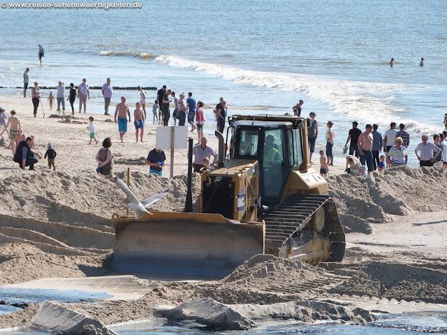 Bagger verteilt den Sand bei der Sandaufspülung am Strand von Westerland auf Sylt