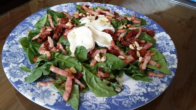 Ensalada de espinacas, beicon queso de cabra y un toque especial de tomates secos en aceite.