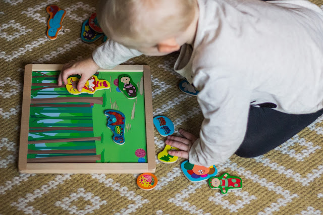 A toddler putting Upsy Daisy on a magnetic board with a forest backdrop