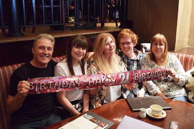 My whole family at a table holding a happy birthday banner
