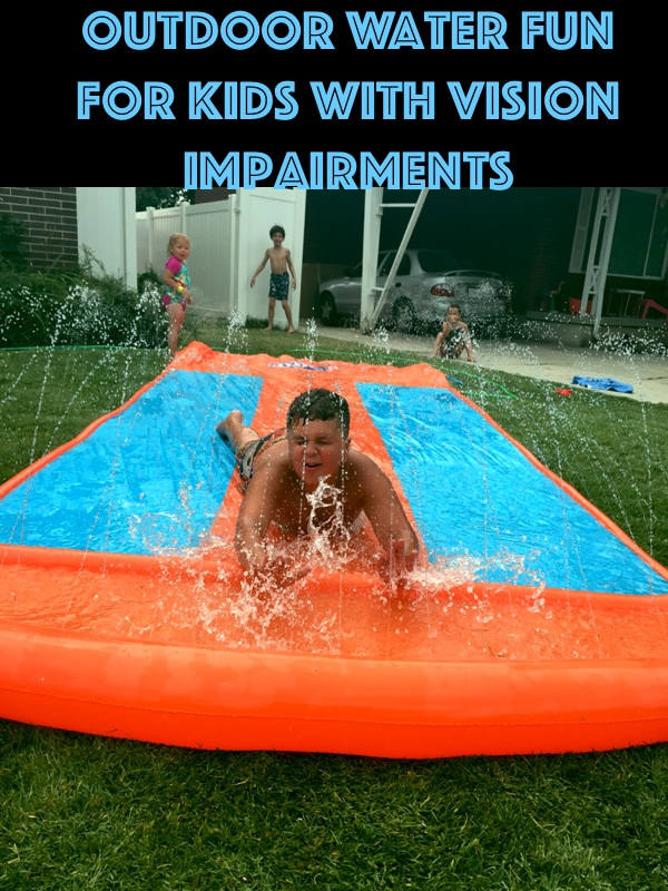 Blind child sliding down a water slide on the grass