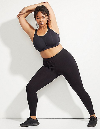 image of a chubby woman with brown skin modeling a black sports bra
