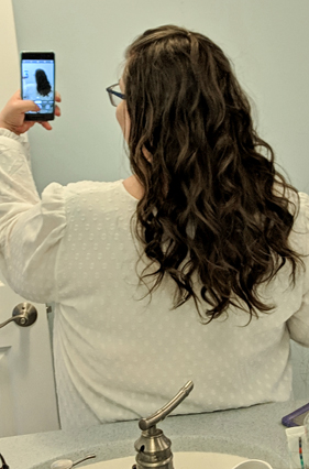 image of me standing in my bathroom mirror, holding up my phone to take a picture of the back of my head, where curls cascade down my back