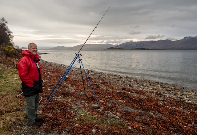 Photo of Phil fishing in the rain on the beach outside the cottage