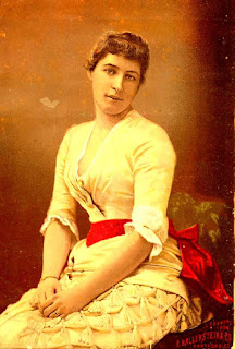 seated young woman posing with yellow dress and red sash