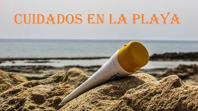 Playa con bronceador sobre la arena y mensaje que dice: cuidados en la playa