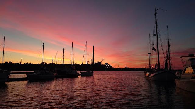 Vaaleanpunainen auringonlasku satamassa, jossa useita purjeveneitä.