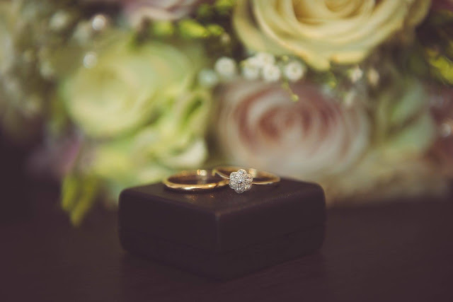 photo by keyhole studios - antique rings on a jewellery box with wedding bouquet in background