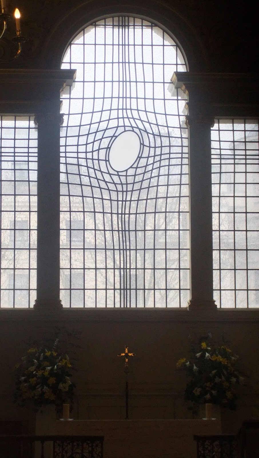 Stained glass window with cross design with a hole in it