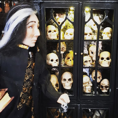 One-twelfth scale doll with black and grey hair in front of a cabinet full of skulls