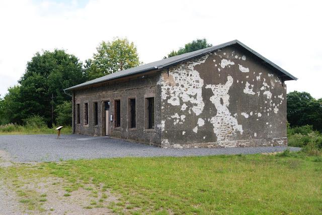 Ein kleines Gebäude mit beschädigter Fassade. Davor steht ein kleines Schild