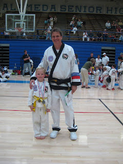 Taekwondo instructor with his student after winning at a tournament