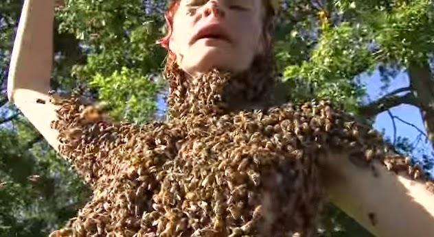 Topless woman dances with 12,000 bees on her body