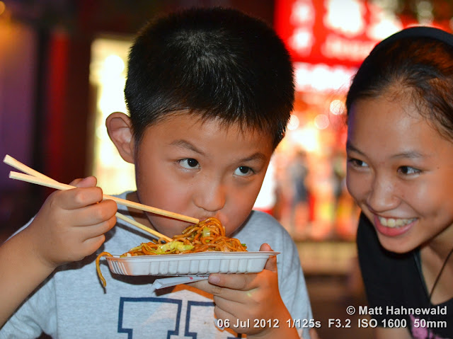 China; Beijing; Donghuamen night market; Chinese food delicacies; Chinese boy eating noodles; chop sticks; fried noodles; spicy noodles; dry noodles; Matt Hahnewald; Facing the World; portrait; street portrait; food; double portrait; duo portrait