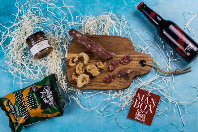 The contents of a gift box showing cut up charcuterie and pork crackling on a wooden chopping board, apple chutney and a bottle of premium lager