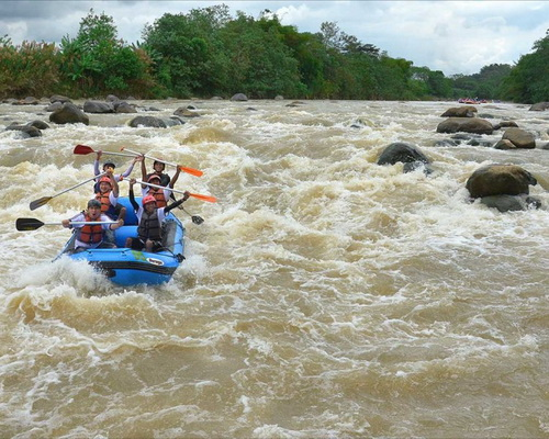 Travel.Tinuku.com Progo River rafting trips enjoy class 5 sensation riding boat on big stone and view Menoreh mountains