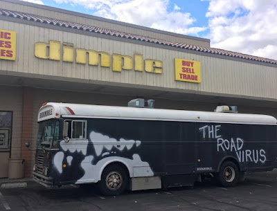 Bookmobile-style bus, black, with irregular white-spot design and spray-paint style logo on side, reading 'The Road Virus.' It is parked in front of a storefront with large yellow lettering on it that reads, 'Dimple.' A smaller sign on the storefront, next to the storefront's lettering reads, 'Buy - Sell - Trade.' The sign is done in red letters against a yellow background.