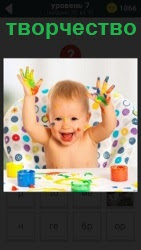 за столом ребенок занимается творчеством и испачкался в краске