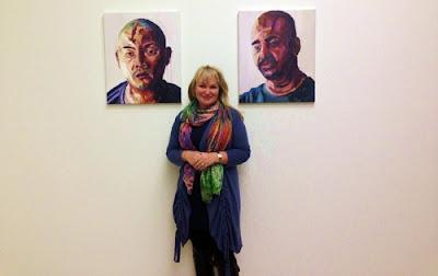 Rev Christie Buckingham with portraits of Andrew Chan and Myuran Sukumaran.