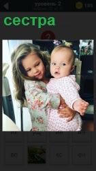 сестра держит на руках маленького ребенка