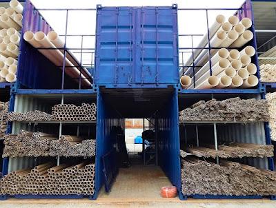 Containers dispostos em formação de tabuleiro de xadrez oferecem abrigo para centenas de barras de PVC.