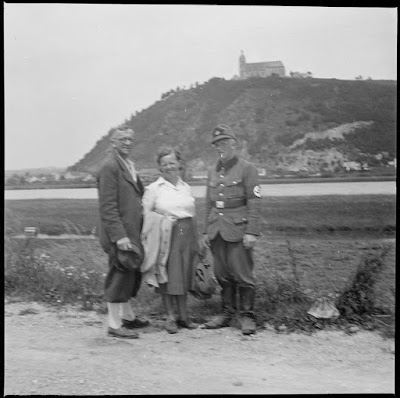 Personen vor dem Bogenberg - eine Person in Uniform mit Hakenkreuzarmbinde
