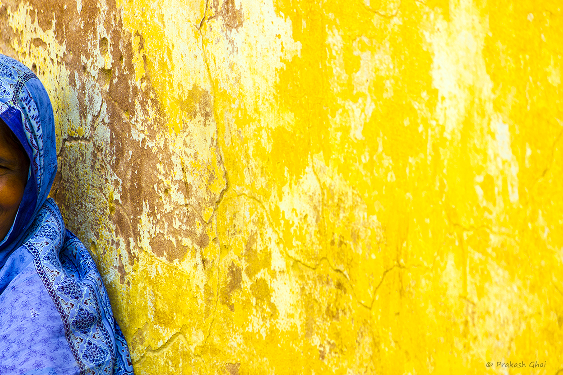 A Minimalist Photo of a Woman in blue saree sitting against a yellow wall at Amber Fort - Jaipur
