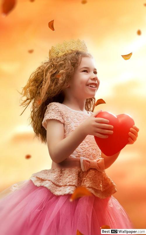 Linda menina com vestes finas, segura um coração vermelho, contente, como se mostrasse para o mundo que o ser humano nasceu para amar e ser feliz.