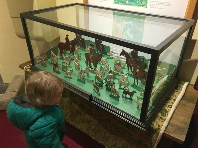 toddler looking at glass case housing wooden dogs and huntsmen on horses