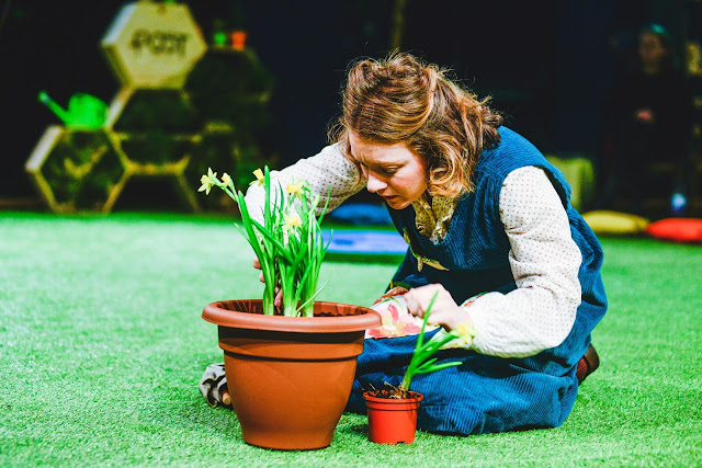 A lady tending to a plant on a grassy floor.