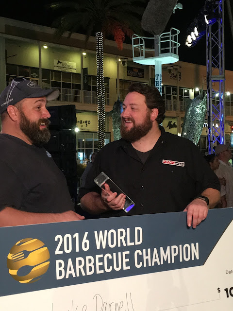 Luke Darnell and Jay Ducote celebrate Luke's $10,000 prize check an title of World Barbecue Champion!