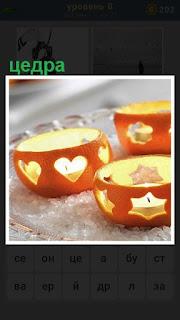 в апельсиновой кожуре цедра с горящими свечами внутри