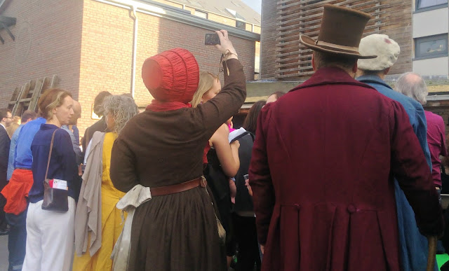 A couple in Victorian costume, one with a mobile phone!