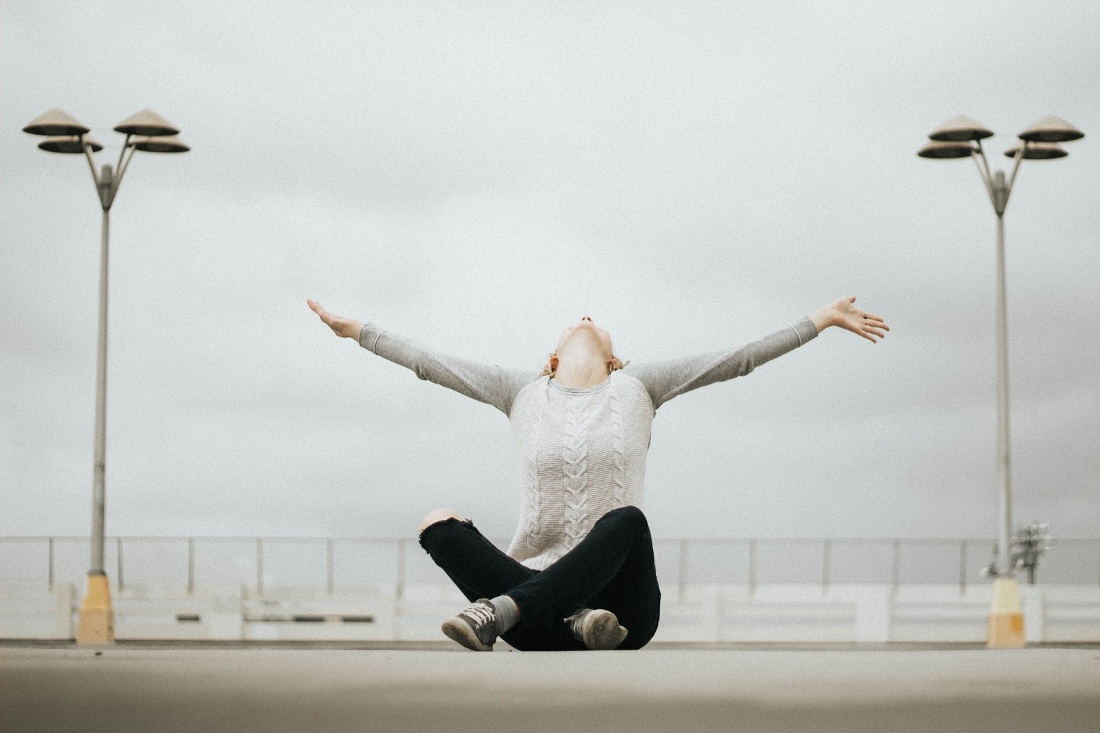 Woman in a grey sweater sitting crosslegged on a seafront with her arms stretched skyward