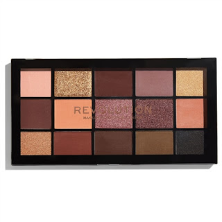 A black rectangular plastic case containing square pans of different colour shimmer and matte shadows including pink, peach, black and gold on a bright background.