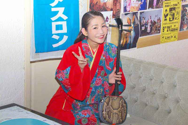 Sari, singer, sanshin, peace sign, smiling
