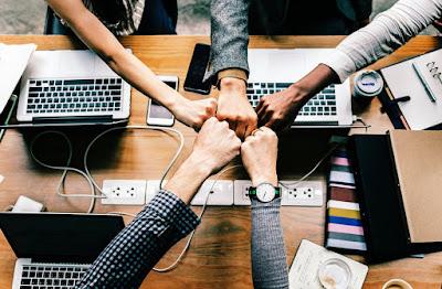 Brazos hacia en centro de una mesa uniendo los puños sobre ordenadores.