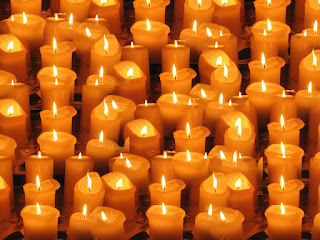A massed collection of thick candles, with some height, each lit and partly consumed. As they have burned, the wax of the body has melted around the flame, and each is thus a slightly different shape.