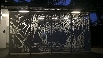 cut-out scenes etched into metal behind which a light shines through