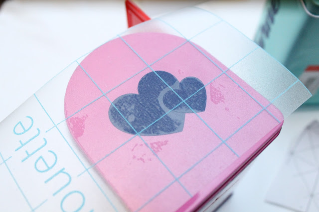 Vinyl hearts on transfer paper stuck to pink mailbox