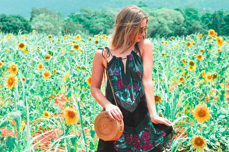 floral velvet boho maxi dress with round rattan basket bag in sunflower fields
