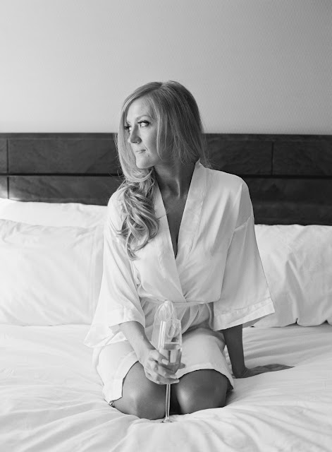 Bride Jenna sits on the bed in a robe with a glass of champagne | Karen Hill Photography