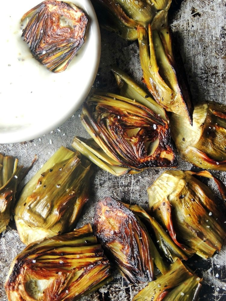 Roasted Baby Artichokes with Lemon Garlic Dipping Sauce in a white bowl on a metal background.