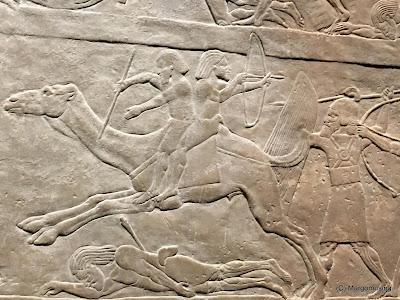 Assyrian stone relief showing soldiers on Camels firing arrows