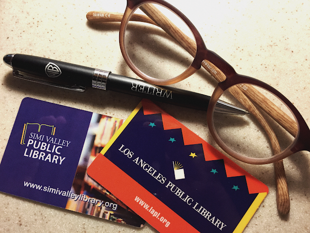 reading glasses a writing pen and 2 library cards