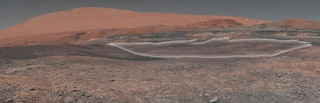 Ảnh góc rộng được chụp từ tàu Curiosity về khu vực dốc đứng của Núi Sharp. Vùng màu trắng trong ảnh (được đánh dấu bằng máy tính) là nơi chứa khoáng vật sét cao mà các nhà khoa học đang mong muốn được khám phá. Để có được hình ảnh góc rộng này, thiết bị Mastcam gắn trên đầu của con tàu đã phải chụp nhiều hình ảnh đơn rồi ghép chúng lại với nhau. Hình ảnh này được chụp vào sol 1931, tức là ngày 11 tháng 1 vừa qua trên Trái Đất. Hình ảnh: NASA/JPL-Caltech/MSSS. Tải hình ảnh.