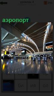 Помещение аэропорта с людьми около стоек и табло информационное