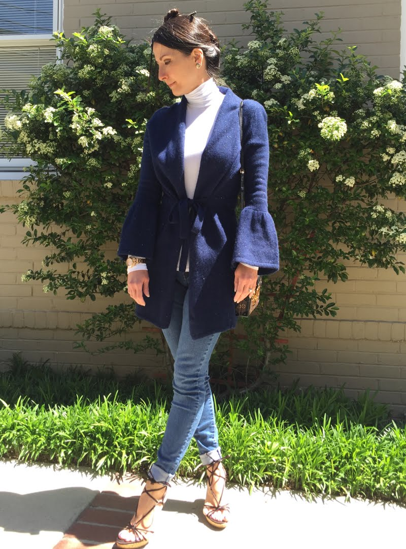 Wearing wool bell sleeve tie front long cardigan with white turtleneck and skinny jeans and lace up sandals.